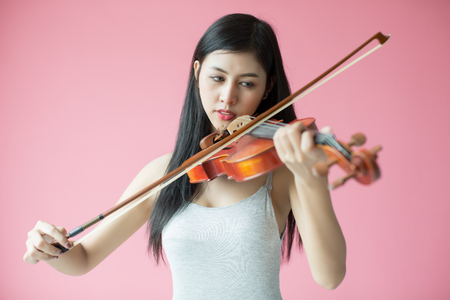 thai musical instrument: beautiful girl playing the violin on pink background