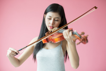 beautiful girl playing the violin on pink background