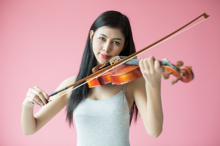 symphonic: beautiful girl playing the violin on pink background