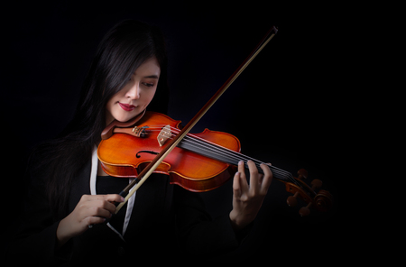 Playing the violin. Musical instrument with hands on dark background. Standard-Bild