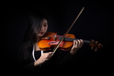 Playing the violin. Musical instrument with hands on dark background. Imagens