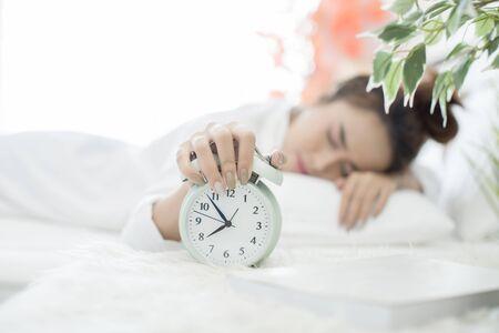Mujer dormida en la cama mientras su alarma muestra la hora temprana en casa en el dormitorio