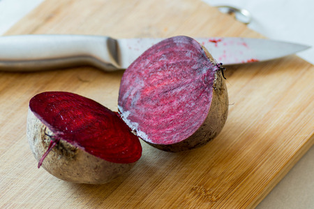 foodies: Sliced beetroot on wooden board with metal knife on the background