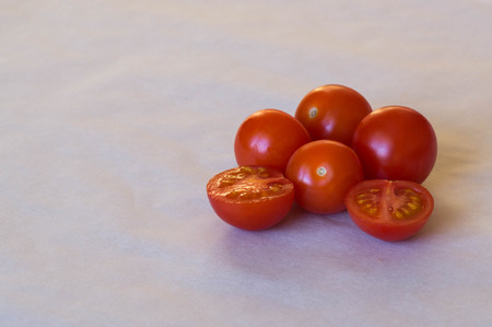 halved  half: Four full and one halved cherry tomato on white background Stock Photo