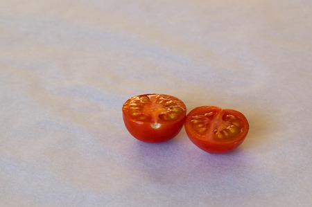tomate cherry: Dos piezas de un tomate cherry reducido a la mitad Foto de archivo