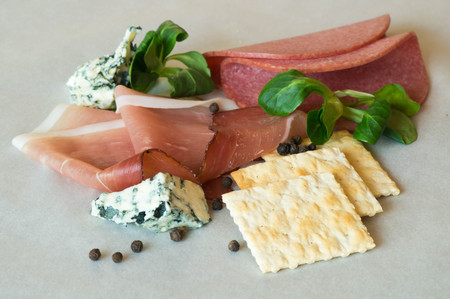 salami slices: Prosciutto and salami slices, with Roquefort cheese and crackers, decorated with black pepper and green salad leafs
