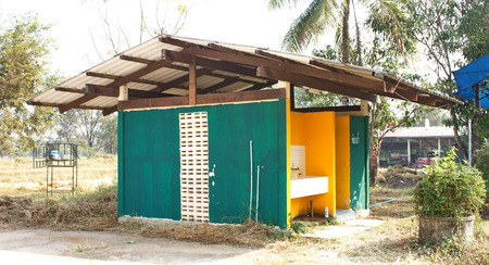 A green concrete toilet hut with open doors photo