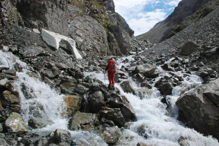 tramping: Woman crossing a river Stock Photo