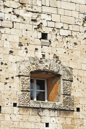 Shattered wall with cracks and bullet holes photo