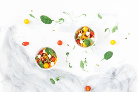Spring salad with rucola, feta cheese, bell pepper and cherry tomatoes. Flat lay, top view