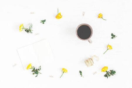 yellow notepad: Workspace with cup of coffee, notepad, yellow flowers on white background. Top view, flat lay Stock Photo
