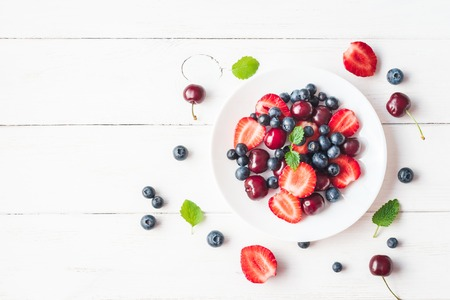 Fruit salad with strawberry, blueberry, sweet cherry on wooden white background. Flat lay, top view
