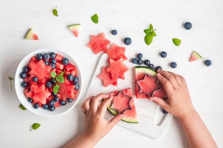 子供たちの手が白いテーブルにサラダを調理、フラット トップ ビュー レイアウト 写真素材