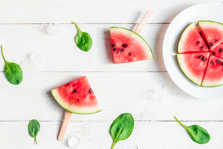watermelon slices on sticks on wooden white background, flat lay, top view Stock Photo