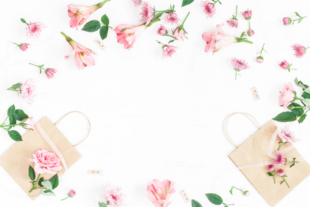 Flowers composition. Gift and pink flowers on white background. Flat lay, top view