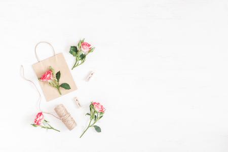 Composizione di fiori Regalo e fiori rosa su fondo bianco di legno. Vista piana, vista dall'alto