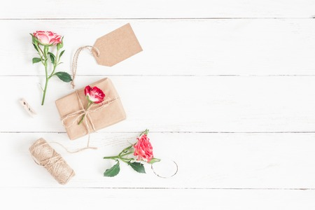 Flowers composition. Gift and rose flowers on wooden white background. Flat lay, top view Stock fotó