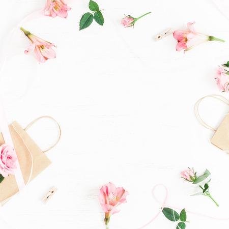 Blumenzusammensetzung. Geschenk und Rose Blumen auf weißem Hintergrund. Flache Lage, Draufsicht
