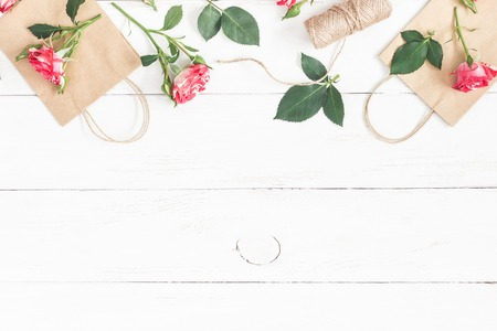 Flowers composition. Gift and rose flowers on wooden white background. Flat lay, top view Zdjęcie Seryjne