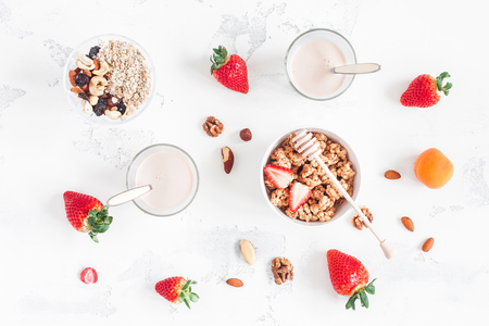 muesli, 요구르트, 딸기, 흰색 배경에 견과류와 함께 건강 한 아침 식사. 평평한 평면, 평면도