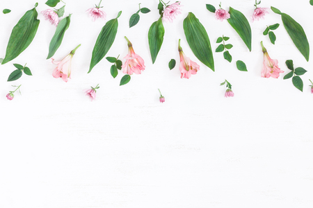 Flowers composition. Border made of pink flowers and leaves. Top view, flat lay