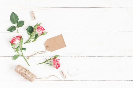 Flowers composition. Label and rose flowers on wooden white background. Flat lay, top view