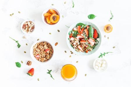 Frühstücken Sie mit muesli, Erdbeersalat, frische Frucht, Orangensaft, Nüsse auf weißem Hintergrund. Gesundes Essen Konzept. Flache Lage, Draufsicht