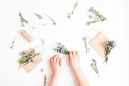 Flowers composition. Child making gifts with flowers. Flat lay, top view