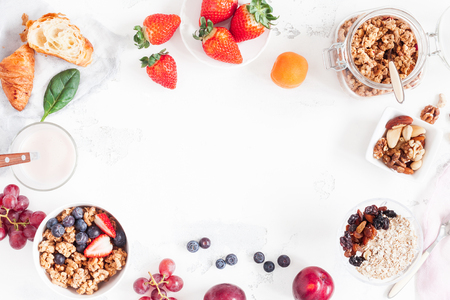 Healthy breakfast with muesli, fruits, berries, nuts on white background. Flat lay, top view Banco de Imagens