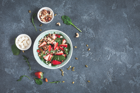 Strawberry salad. Spinach leaves, sliced strawberries, nuts, feta cheese on dark background. Healthy food concept. Fat lay, top view
