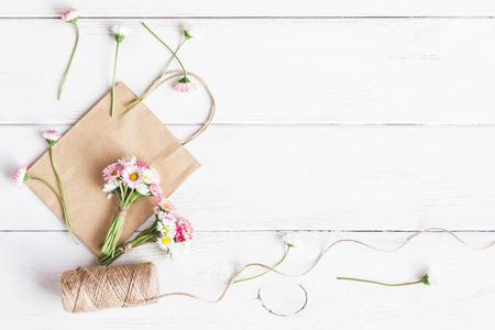デイジーの花、紙袋の小さな花束をワークスペース。作成します。平面図、平面レイアウト 写真素材