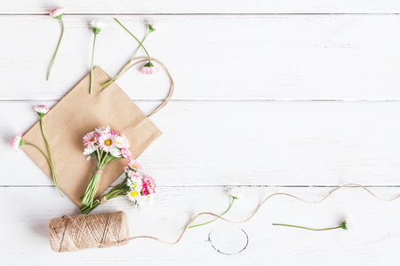 Werkruimte met kleine boeketten van madeliefjebloemen, papieren zakken. Creation. Bovenaanzicht, plat leggen Stockfoto