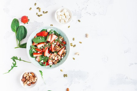 Strawberry salad. Spinach leaves, sliced strawberries, nuts, feta cheese on white background. Healthy food concept. Fat lay, top view Фото со стока