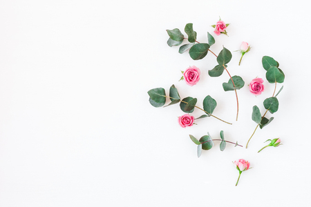 Flowers composition. Pattern made of rose flowers and eucalyptus branches. Flat lay, top view