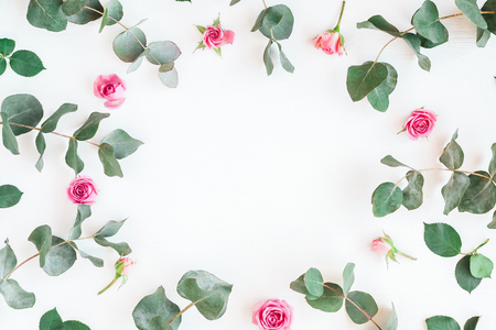 Flowers composition. Frame with rose flowers and eucalyptus branches. Flat lay, top view