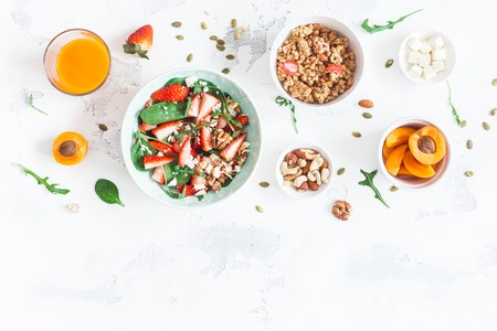 Breakfast with muesli, strawberry salad, fresh fruit, nuts on white background. Healthy food concept. Flat lay, top view