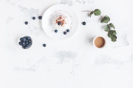 一杯のコーヒー、甘いデザート、ブルーベリーと朝食します。フラット横たわっていた、トップ ビュー
