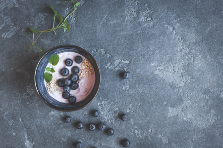 Blueberry yogurt with muesli on dark background. Healthy food concept. Flat lay, top view Stock Photo