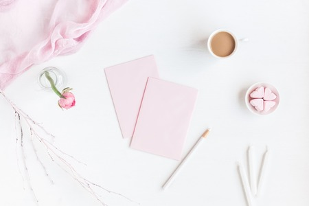 Feminine workspace with notebook, cup of coffee, paper blank, pink flower, pencil. Business concept. Flat lay, top view Zdjęcie Seryjne - 73191338