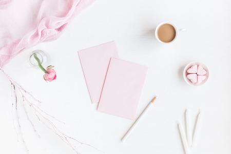 Vrouwelijke werkruimte met notitieboekje, kopje koffie, papierblanco, roze bloem, potlood. Business concept. Plattegrond, bovenaanzicht