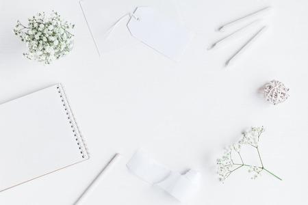 Werkruimte met notitieboekje, document spatie, gypsophilabloemen, potloden. Bruiloft concept. Plat leggen, bovenaanzicht