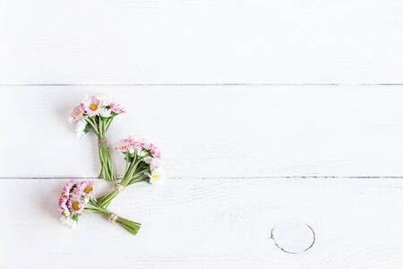 bouquet of daisy flowers on wooden white background, top view, flat lay Zdjęcie Seryjne