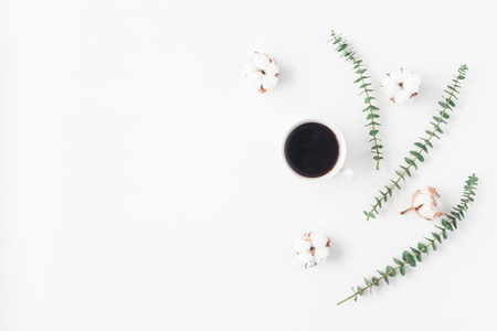 Workspace with cup of coffee, cotton flowers, eucalyptus branches. Flat lay, top view Stock Photo