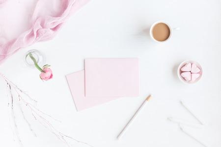 Przestrzeń robocza kobieca z notesem, filiżankę kawy, papier pusty, różowy kwiat, ołówek. Pomysł na biznes. Płaski, górny widok