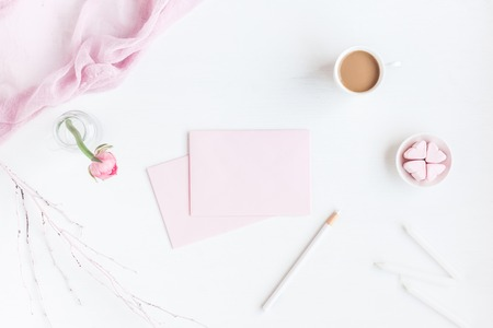 Feminine workspace with notebook, cup of coffee, paper blank, pink flower, pencil. Business concept. Flat lay, top view