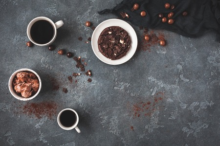 Cups of coffee, chocolate cake and chocolate ice cream on dark background. Flat lay, top view, copy space
