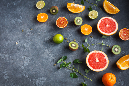 Colorful fresh fruit on dark background. Orange, tangerine, lime, kiwi, grapefruit. Fruit background. Summer food concept. Top view, copy space