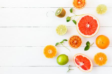 과일 배경입니다. 흰색 테이블에 다채로운 신선한 과일입니다. 오렌지, 귤, 라임, 키위, 자몽. 평평한 가로, 평면도, 복사 공간