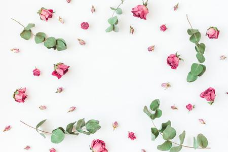 Blumen Zusammensetzung. Getrocknete Rosenblüten und Eukalyptuszweige. Flache Lage, Draufsicht Standard-Bild - 74625954