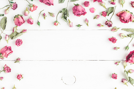Flowers composition. Frame made of dried rose flowers on white wooden background. Flat lay, top view